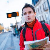 Just arrived: handsome young man studying a map on a bus stop in front of a train station