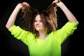 stock photo of character traits  - Grimacing young crazy woman making silly face pulling hair on black background - JPG