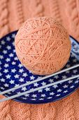 One ball of pink yarn and knitting needles on a blue plate with asterisks