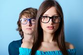 Fashionable young couple wearing trendy glasses, over blue