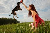 foto of frisbee  - Beautiful young woman playing with her dog in park - JPG