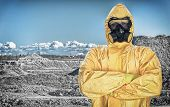 Worker In Protective Chemical Suit Over Mountains.
