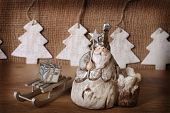 picture of figurine  - christmas card with vintage santa clay figurine on wooden and canvas background - JPG