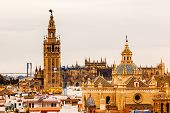 stock photo of christopher columbus  - Giralda Spire Bell Tower Seville Cathedra Cathedral of Saint Mary of the See Church of El Salvador Seville Andalusia Spain - JPG