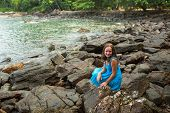 Teengirl in a blue dress in the rocks of the sea coast.