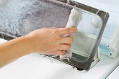 stock photo of lent  - Horizontal photo of female hand taking the lent out from dirty air filter of the dyer machine - JPG