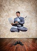 stock photo of levitation  - Levitation by Indian businessman with laptop in lotus pose and shoes on the floor at textured background - JPG