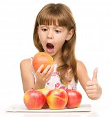 Portrait of a little girl with red apples showing thumb up sign, isolated over white