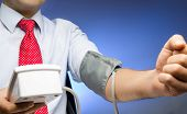Businessman with blood pressure cuff on arm