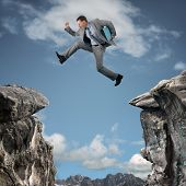 stock photo of crevasse  - Businessman leap of faith concept for business adversity - JPG