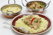 View of balti chicken pasanda curry served on a bed of saffron rice, garnished with coriander leaves and a red chilli.