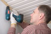 Contractor installing molding to ceiling using cordless power screw driver