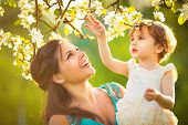 stock photo of mother baby nature  - Happy woman and child in the blooming spring garden - JPG