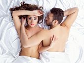 Image of weary young lovers lying on silk sheets