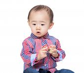 Little Asian boy holding wooden toy block and looking aside