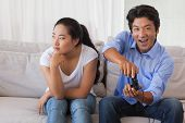 Man ignoring his girlfriend playing video games at home in the living room