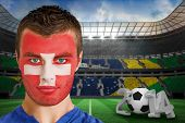 Composite image of serious young switzerland fan with facepaint against large football stadium
