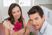 Close-up of a happy young man and woman with flowers at home