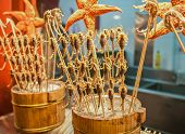 stock photo of scorpion  - fried scorpions on a stick on street food stall at Wangfujing Snack Street in Dongcheng District Beijing China - JPG