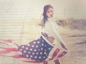 Beautiful young woman holding flag of United States of America in desert background.