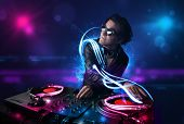 Young disc jockey playing music with electro light effects and lights