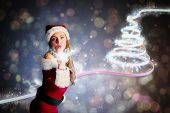 Sexy santa girl blowing a kiss against dark abstract light spot design