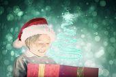 Festive boy opening gift against blue abstract light spot design