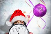 Woman worried at the time against blurred christmas decorations