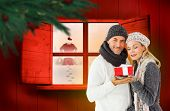 Happy winter couple with gift against festive fir branch with baubles