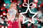 Pretty blonde showing wad of cash against blurred christmas background