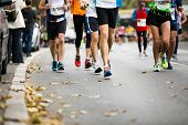 picture of competing  - Marathon running race people feet on autumn road - JPG