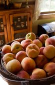 A Basket Full Of Peaches Sitting On Counter