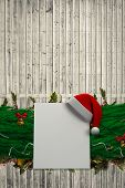 Fir branch christmas decoration garland against digitally generated grey wooden planks