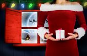 Pretty girl in santa outfit holding gift against santa delivery presents to village