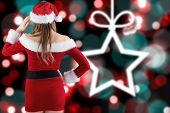 Sexy santa girl with hand on hip against blurred christmas background