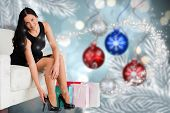 Woman sitting with shopping bags against baubles hanging over christmas scene