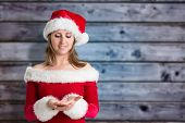Pretty girl in santa outfit against blurry wooden planks