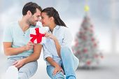Young couple holding gift against blurry christmas tree in room