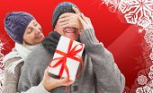 Mature woman surprising partner with gift against christmas themed snow flake frame