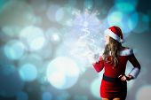 Pretty girl in santa costume holding hand out against light glowing dots design pattern