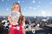 Pretty blonde showing wad of cash against city skyline