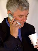 Handsome Senior businessman on phone with Coffee