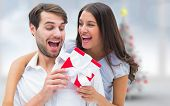 Woman surprising boyfriend with gift against blurry christmas tree in room