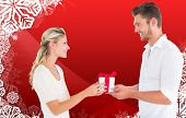 Young couple with gift against christmas themed snow flake frame