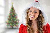 Sexy santa girl smiling at camera against blurry christmas tree in room