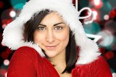 Pretty girl smiling in santa outfit against blurred christmas background