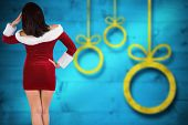 Rear view of sexy santa girl against blurred christmas background
