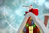 Santa sitting on roof of cottage against blurred christmas background