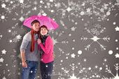 Couple standing underneath an umbrella against snowflake wallpaper pattern