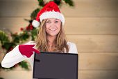 Festive blonde pointing to laptop against blurred holly on wood